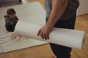 Father holding exercise mat while baby playing in backgroundの写真素材 [FYI02236458]