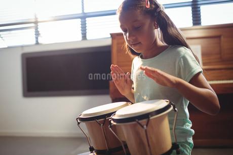Girl playing bongo drums in classroomの写真素材 [FYI02236471]