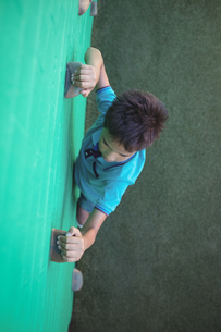 Boy gripping climbing holds on wallの写真素材 [FYI02236488]