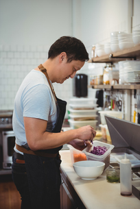 Chef adding chopped cabbage into bowl in commercial kitchenの写真素材 [FYI02236507]