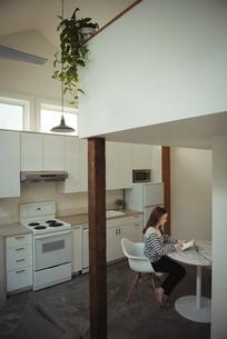 Woman using digital tablet in kitchenの写真素材 [FYI02236538]