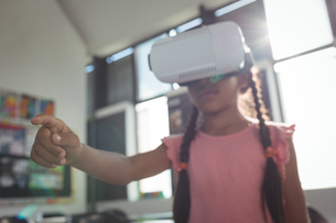 Girl wearing virtual reality simulator in classroomの写真素材 [FYI02236542]