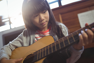 Concentrated girl practicing guitarの写真素材 [FYI02236544]