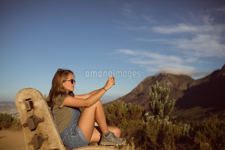 Young woman taking picture from mobile phoneの写真素材 [FYI02236571]