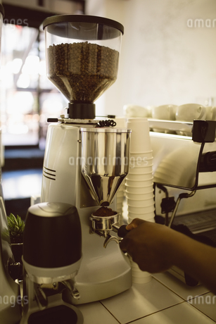 Hand of barista holding portafilter under coffee machineの写真素材 [FYI02236586]