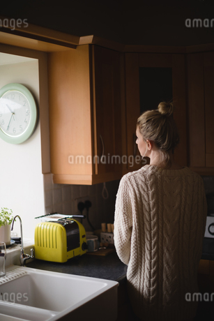 Thoughtful woman in kitchen at homeの写真素材 [FYI02236618]