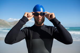 Athlete wearing swimming goggles by seaの写真素材 [FYI02236641]