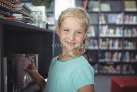 Portrait of girl choosing book from shelfの写真素材 [FYI02236651]