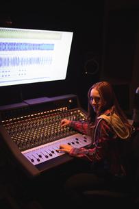 Portrait of female audio engineer using sound mixerの写真素材 [FYI02236659]
