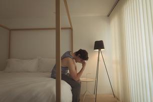 Upset man sitting on bedの写真素材 [FYI02236694]