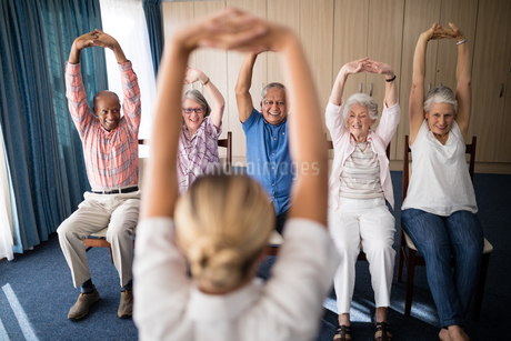 Cheerful senior men and women exercising with female doctorの写真素材 [FYI02236729]