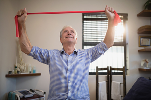 Smiling senior male patient pulling red resistance band while looking upの写真素材 [FYI02236738]