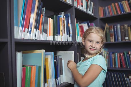 Girl choosing book from shelfの写真素材 [FYI02236761]