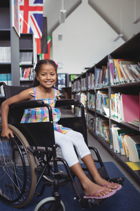 Smiling girl sitting on wheelchair in libraryの写真素材 [FYI02236791]