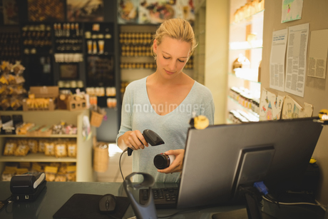 Saleswoman scanning product in storeの写真素材 [FYI02236805]