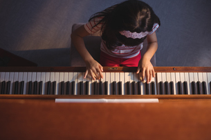 Overhead view of elementary girl playing piano in classroomの写真素材 [FYI02236810]