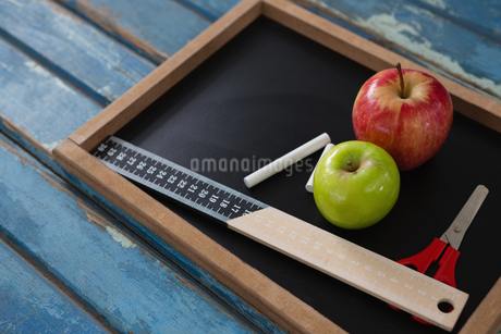 School supplies and slate on wooden tableの写真素材 [FYI02236838]