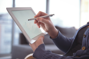 Woman using digital tablet while sitting at homeの写真素材 [FYI02236844]