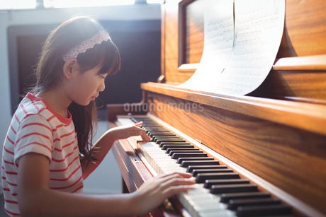 Side view of girl practicing piano in classroomの写真素材 [FYI02236880]