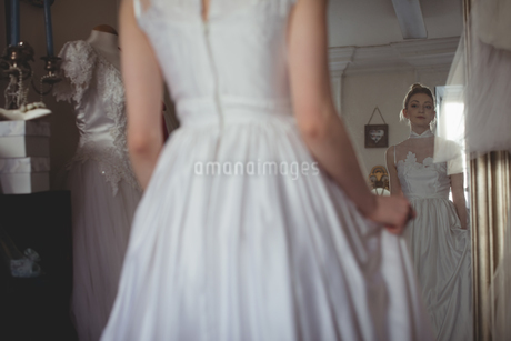 Young bride in a white dress looking into mirrorの写真素材 [FYI02236890]