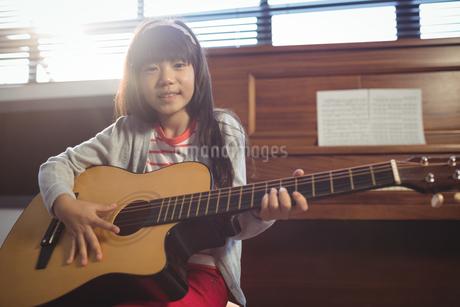 Portrait of girl practicing guitarの写真素材 [FYI02236897]