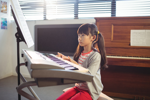 Concentrated girl looking at notes while practicing pianoの写真素材 [FYI02236902]