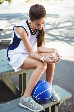 Woman using smart phone while sitting on picnic tableの写真素材 [FYI02236914]