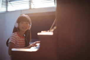 Portrait of smiling girl wearing headphones while practicing pianoの写真素材 [FYI02236927]
