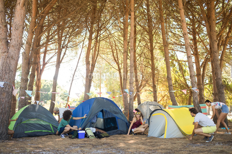 Friends setting up colorful tents at campsiteの写真素材 [FYI02236941]