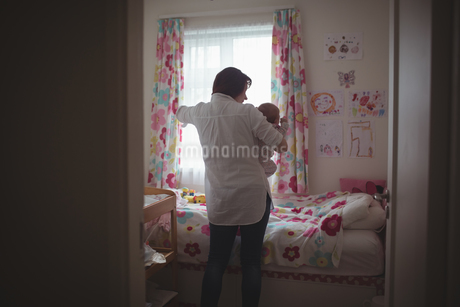 Mother with baby standing by window in bedroomの写真素材 [FYI02236942]