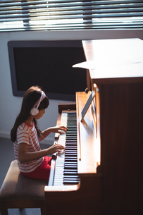 High angle side view of girl wearing headphones while practicing pianoの写真素材 [FYI02236950]