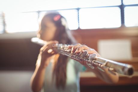 Girl practicing flute in classroomの写真素材 [FYI02236951]