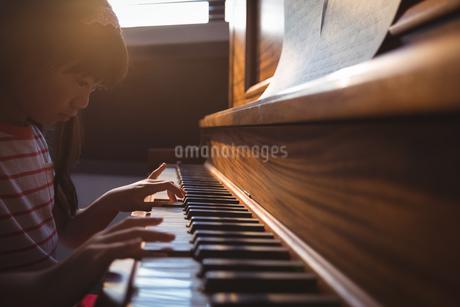 Focused girl practicing piano in classroomの写真素材 [FYI02236956]