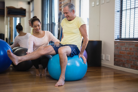 Female therapist helping senior male patient doing leg exercise on blue ballの写真素材 [FYI02236986]