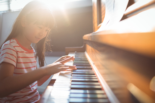 Smiling girl practicing piano in classroomの写真素材 [FYI02237007]