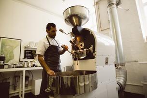 Man operating coffee roasting machineの写真素材 [FYI02237010]