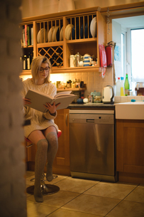 Woman reading a book in kitchenの写真素材 [FYI02237018]