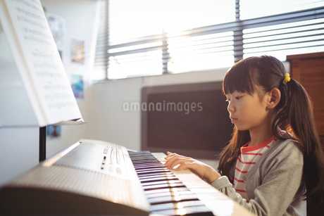 Concentrated girl practicing piano in classの写真素材 [FYI02237022]