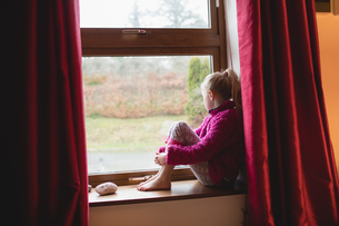 Thoughtful girl sitting on window sillの写真素材 [FYI02237026]