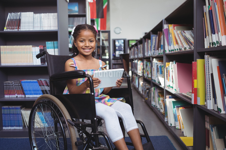 Girl on wheelchair smiling while holding digital tabletの写真素材 [FYI02237057]