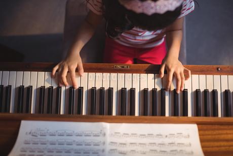 Overhead view of girl practicing piano in classroomの写真素材 [FYI02237076]