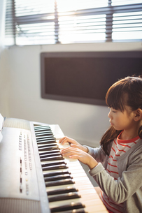High angle view of concentrated girl practicing piano in classの写真素材 [FYI02237082]
