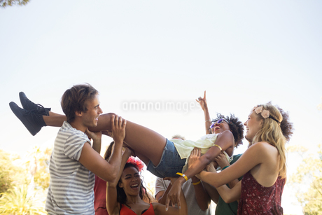 Playful friends carrying happy womanの写真素材 [FYI02237102]