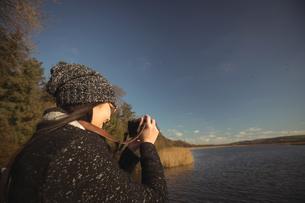 Woman taking photos on digital camera in parkの写真素材 [FYI02237111]