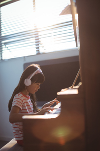 Concentrated girl wearing headphones while practicing piano by windowの写真素材 [FYI02237117]