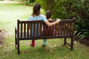 Rear view of woman and girl sitting on wooden benchの写真素材 [FYI02237123]
