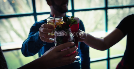 Friends toasting glasses of drinks in barの写真素材 [FYI02237131]