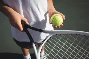 Midsection of girl holding tennis racket and ballの写真素材 [FYI02237148]