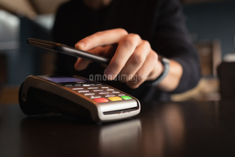 Man paying bill through smartphone using NFC technologyの写真素材 [FYI02237189]