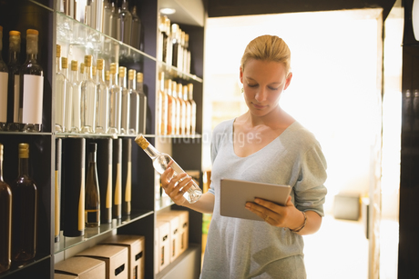 Saleswoman holding digital tablet and bottle in supermarketの写真素材 [FYI02237244]